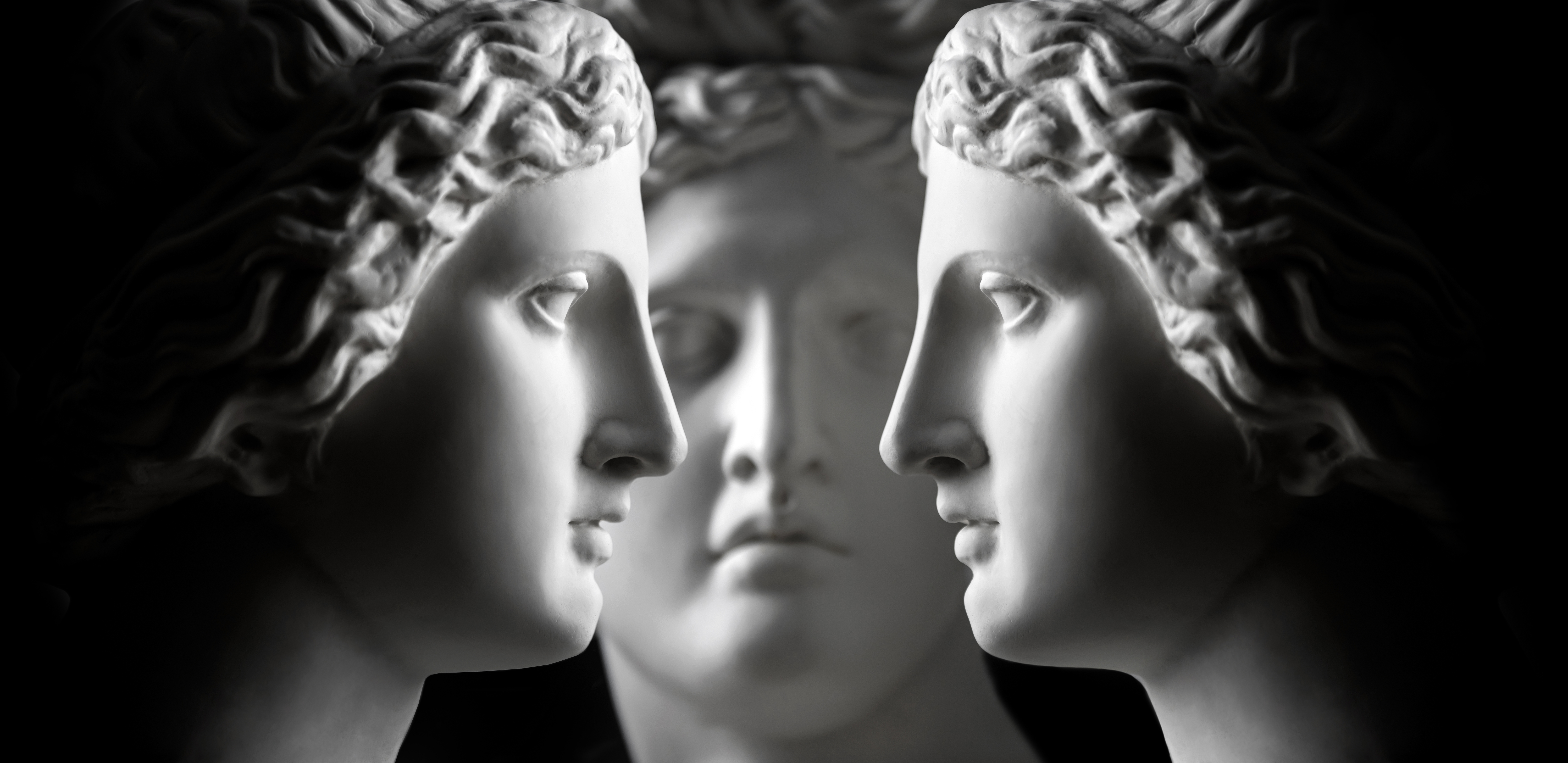 Three marble statue heads (two of Aphrodite and one of Apollo) face each other