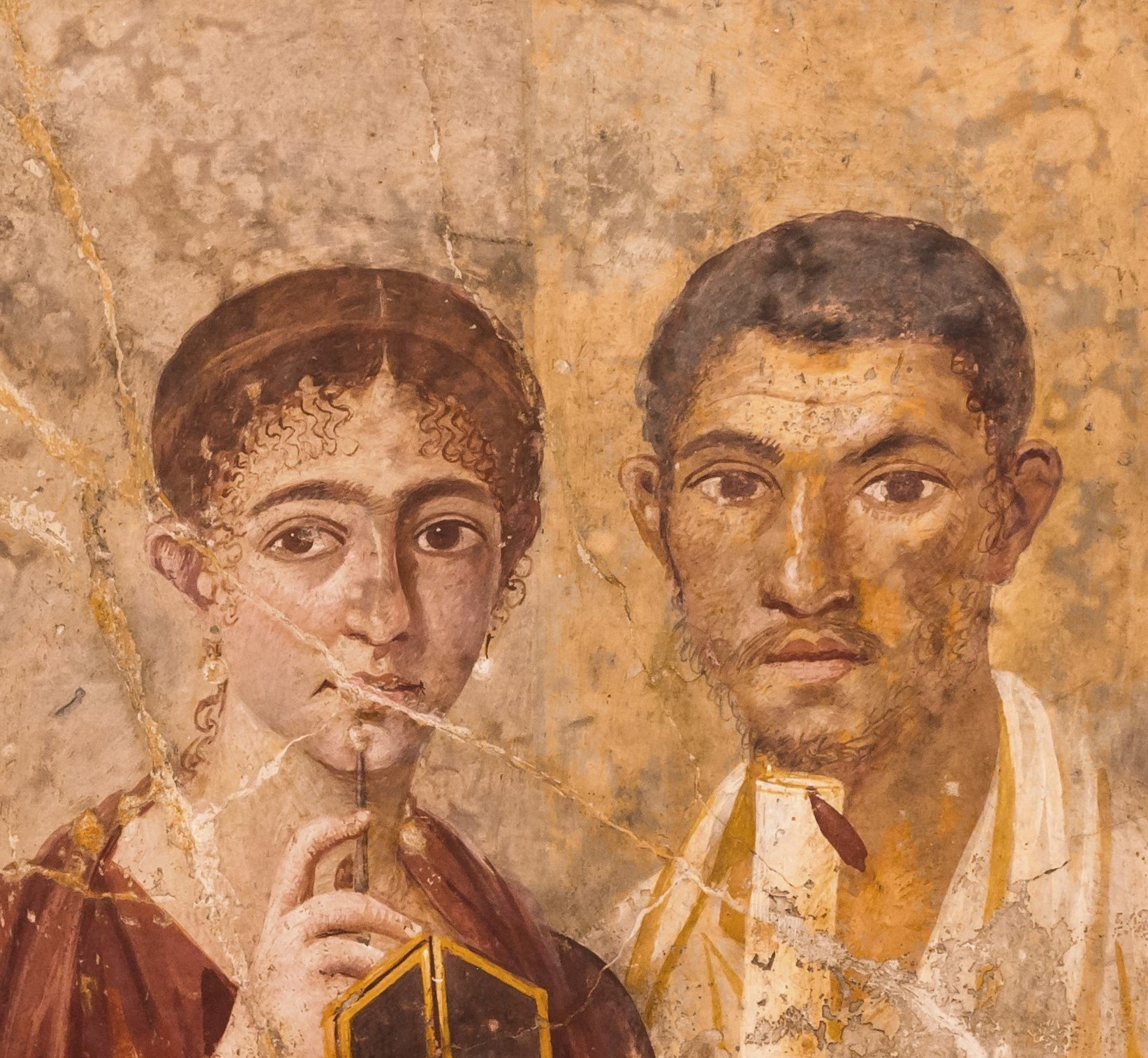 Roman fresco from Pompei depicting a man holding a scroll and a woman holding a stylus and wax tablet.
